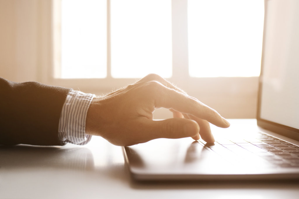 Hands of a businessman using laptop on the internet